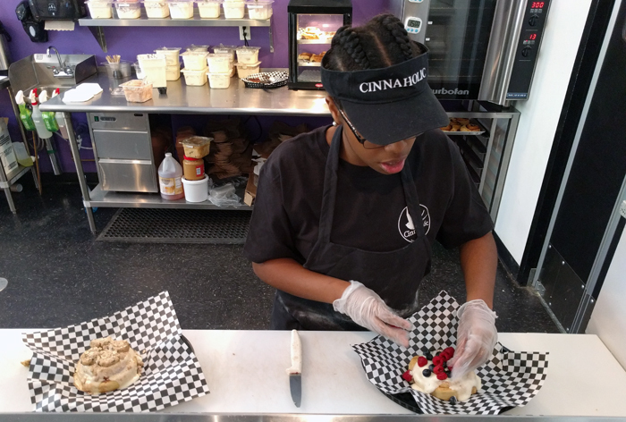 An associate sprinkles fresh berries on a frosted bun.